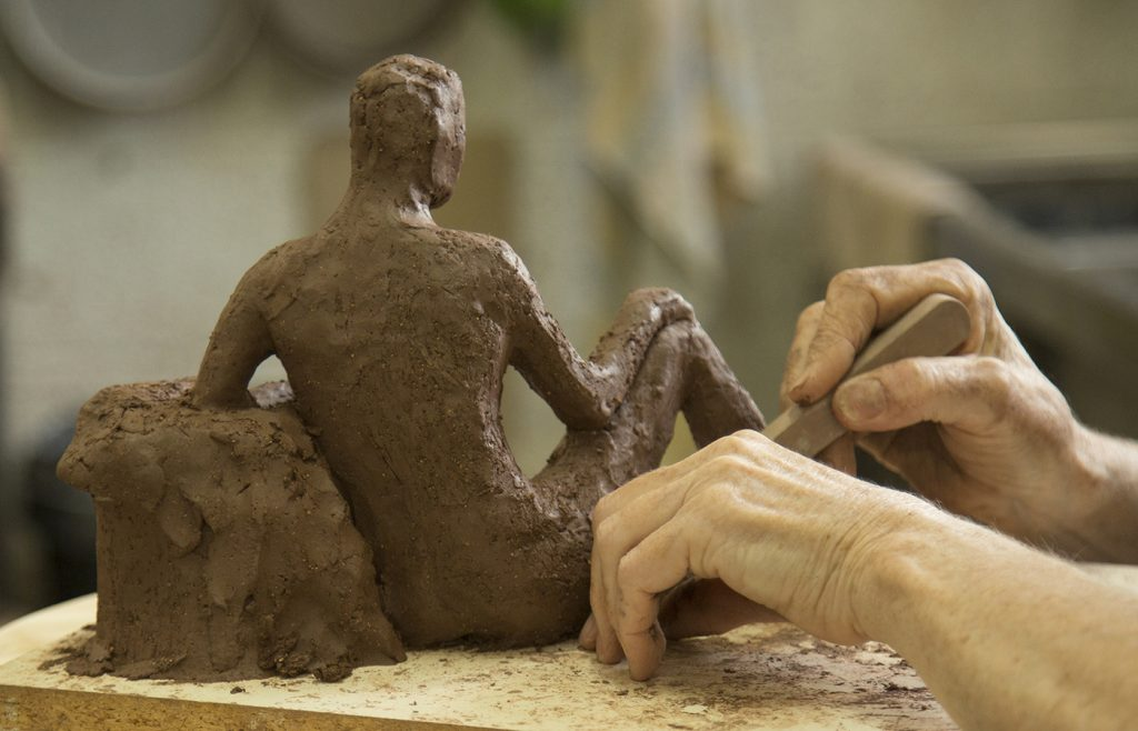 Hands sculpting red clay figure